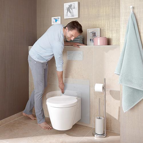 Ein Mann verstellt in einem modernen Bad die Höhe des WCs